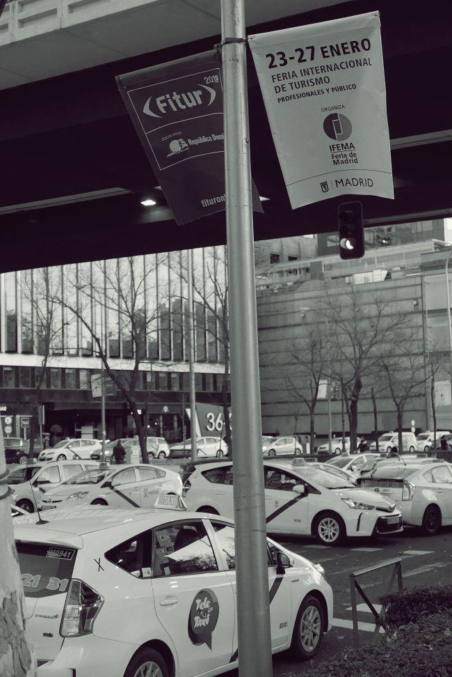 Taxistas parados bajo un anuncio de Fitur en Madrid